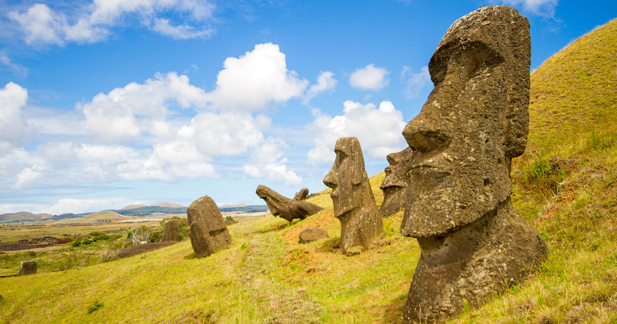 A moai sculpture sits partially buried in green grass on Easter Island