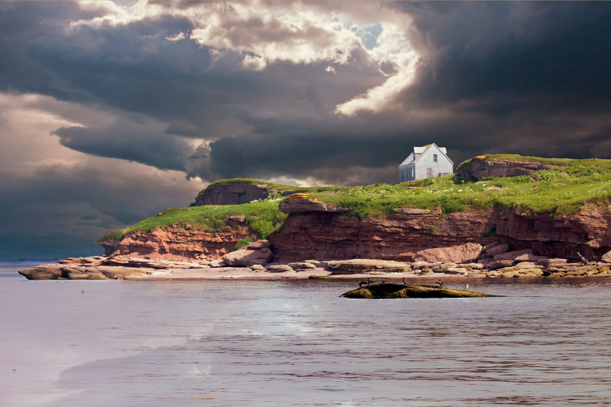 A lone farmhouse sits on the edge of a cliff against a moody sky near Perce, Quebec on the Gaspe Peninsula