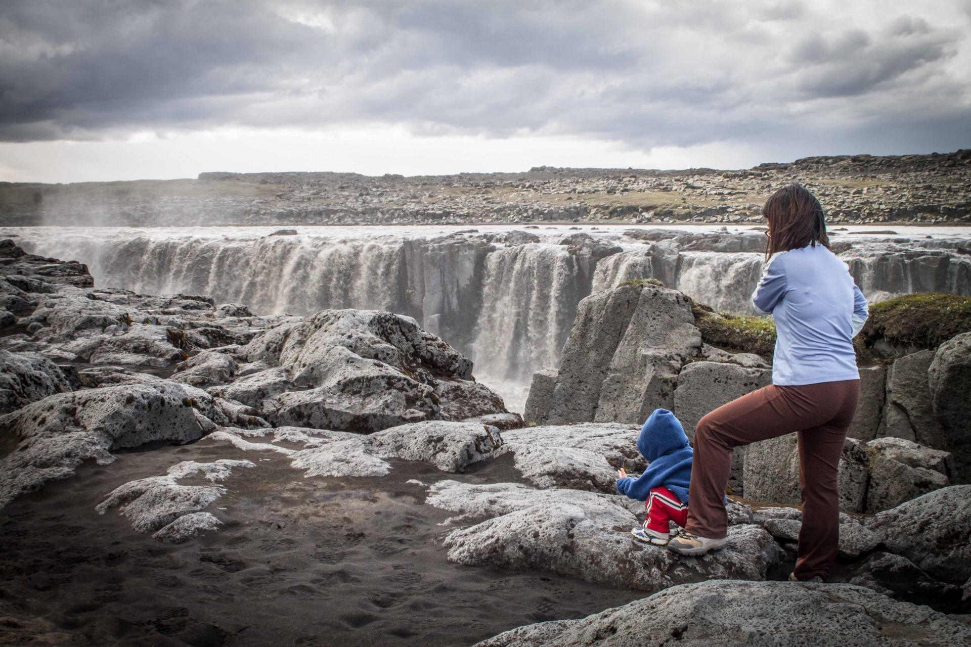 A woman and toddler watch a wide and roaring waterfall in Iceland - Icelandic Highlands