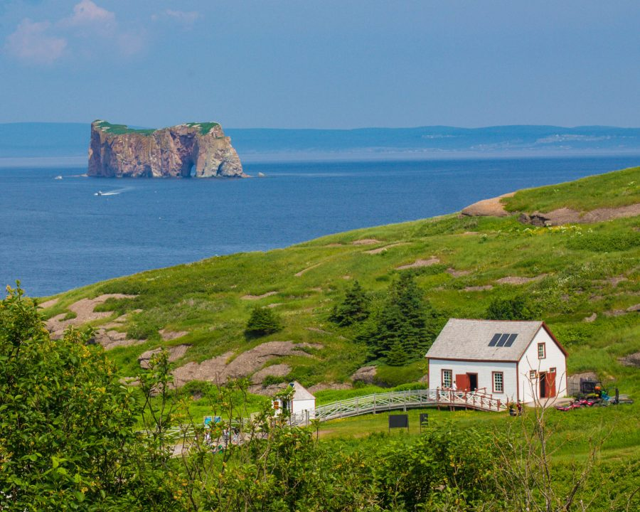 A colorful farmhouse on Bonaventure Island and Perce rock in the distance
