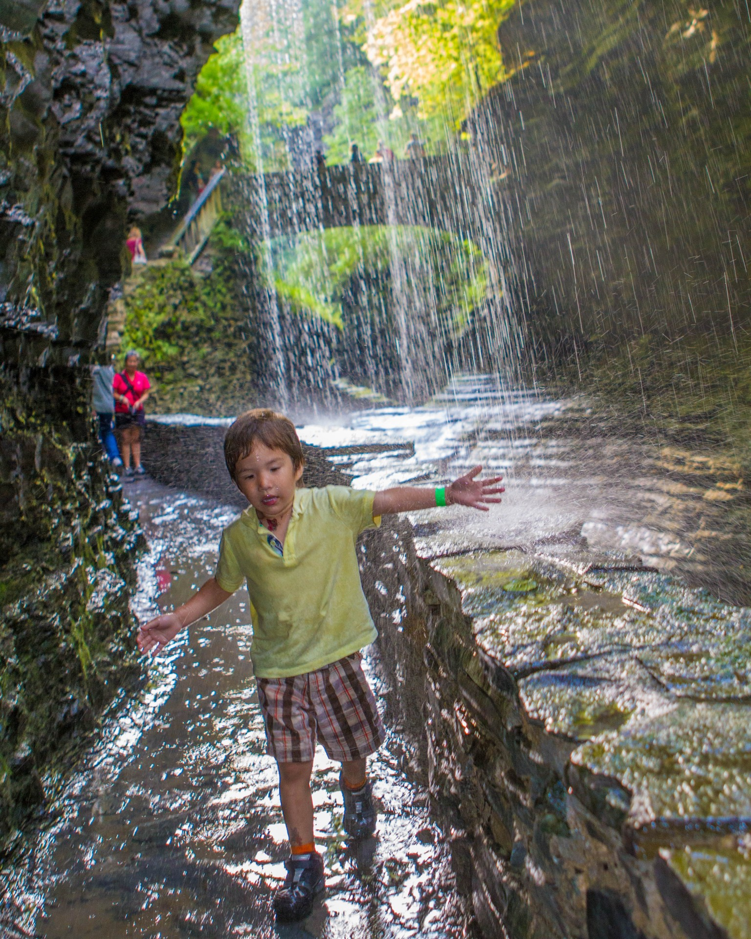 Boy playing under Rainbow Falls in Wakins Glen State Park.