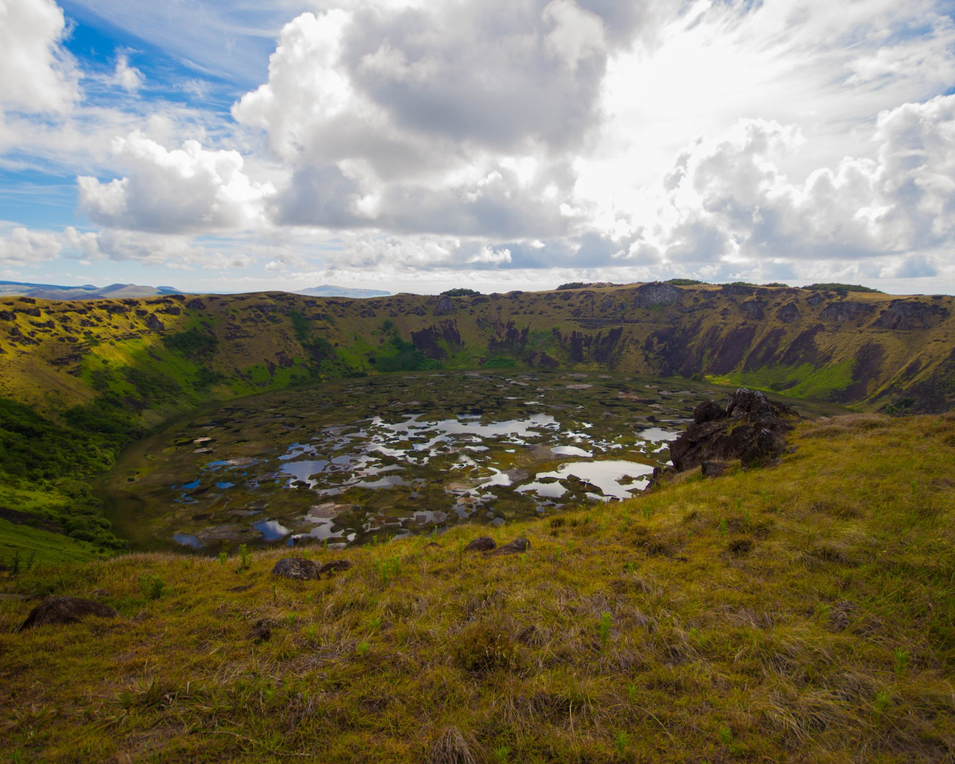 A colourful marsh reflects the clouds within a volcanic crater surrounded by lush green cliffs