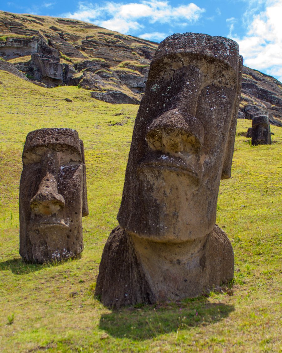 two moai sit partially sunken in the green grass on a mountainside of Easter Island. In the background rocks and other partially sunken moai can be seen.