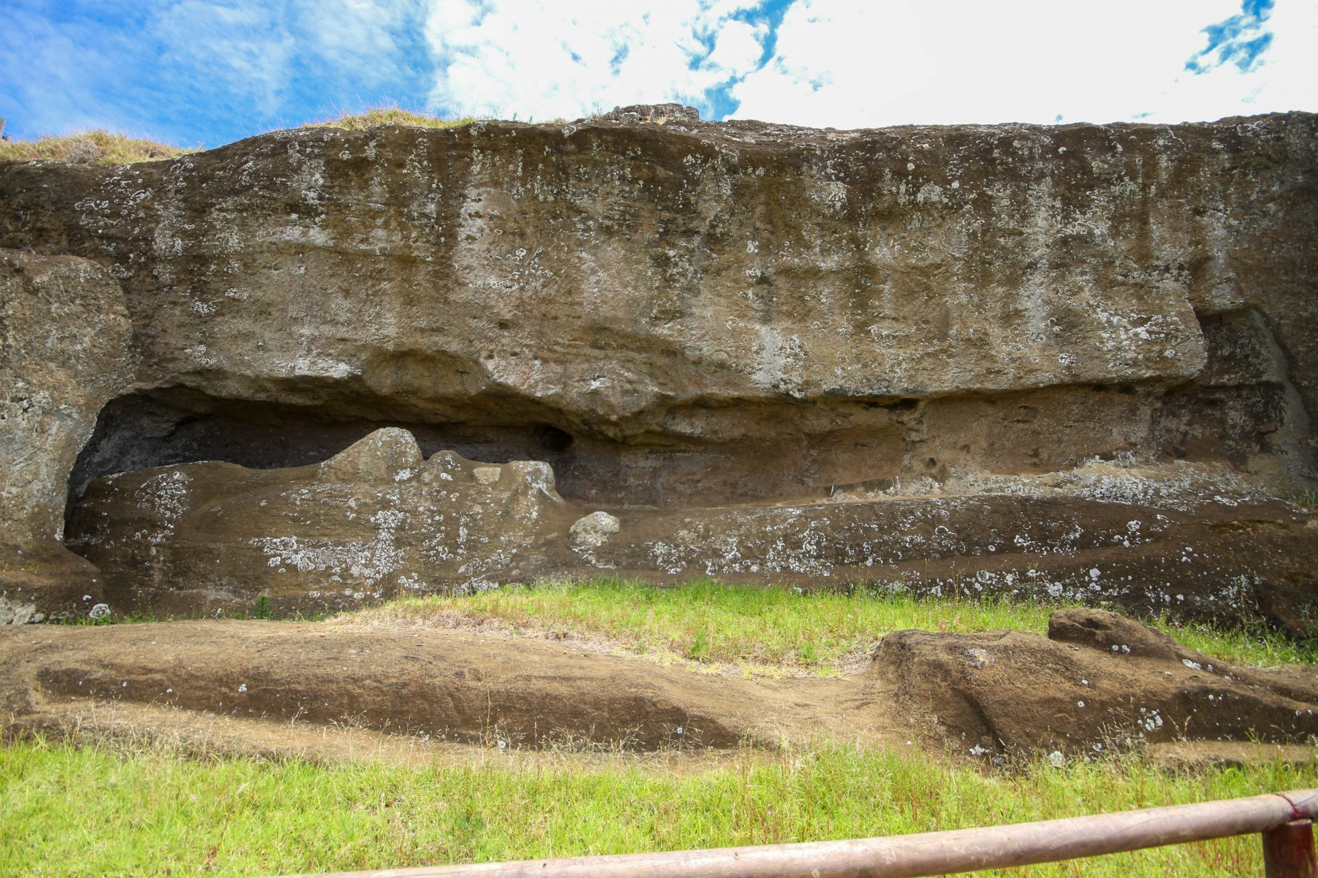 two moai lie incomplete at Rano Raraku on Easter Island. One sits partially carved out of a cliff, while a second lies on the ground in front of it