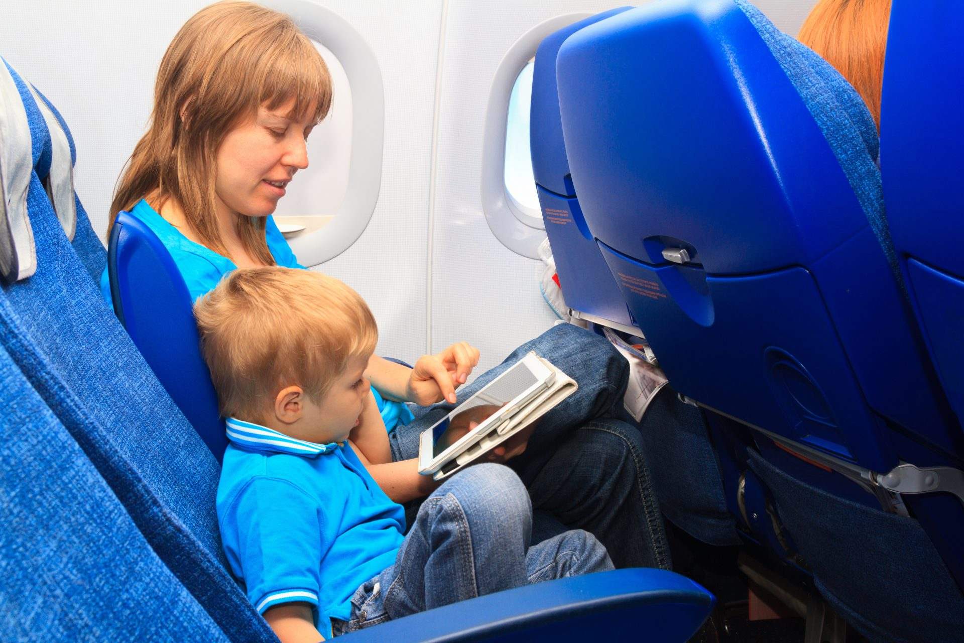Mother plays games on a tablet with her young son as they fly on an airplane - - Flying with a baby
