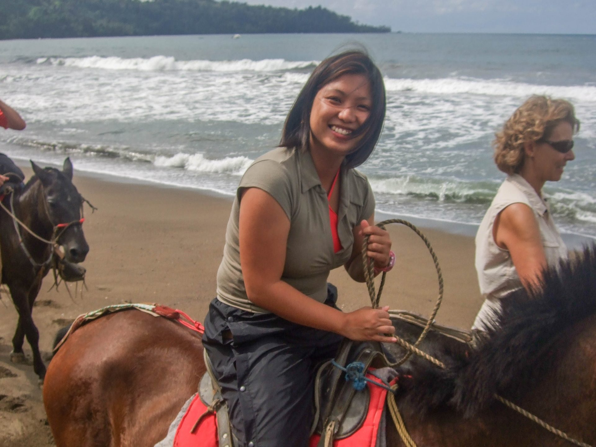 A young woman smiles at the camera as she rides a horse along the beach - finding paradise on the Osa Peninsula