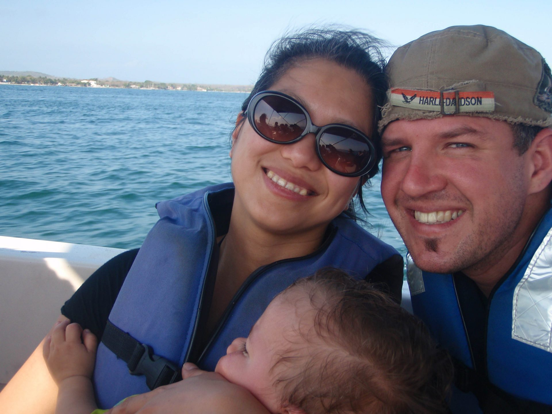 Mom holding her son with father beside her while on a boat to Pirate Island.