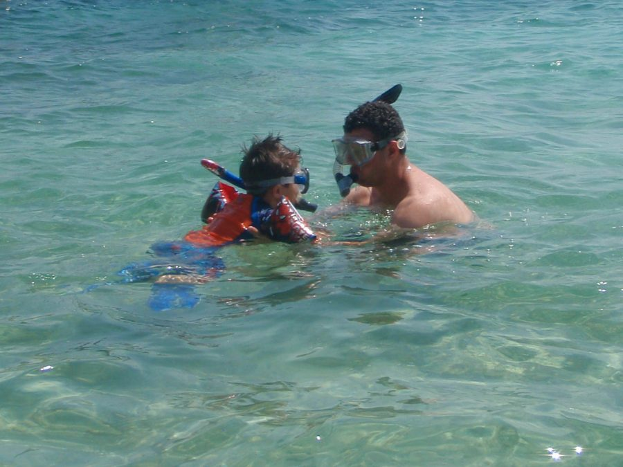 Boy learns how to snorkel from man.