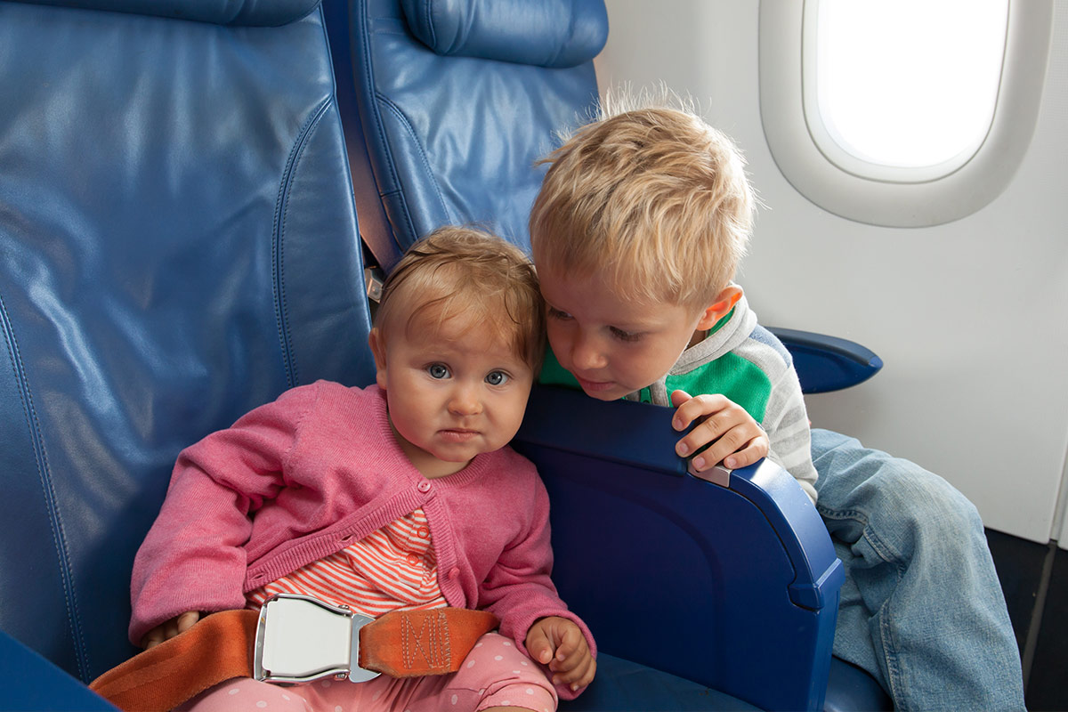 Toddler looking over a plane seat at his baby sister