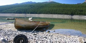 A wooden canoe anchored by a metal pipe sits in a crystal clear lake with forest and mountains in the background - Bucket list destinations in Canada