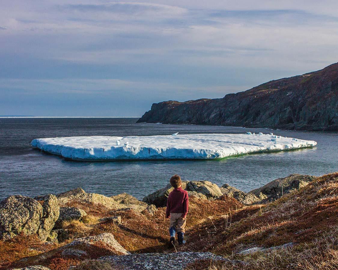 Boy walking towards Iceberg in St Anthony Newfoundland