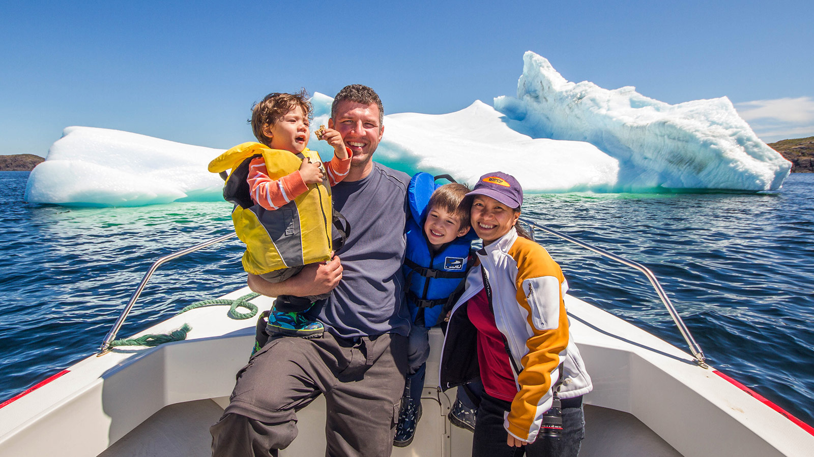 A young family smiles from the bow of a small boat while a large iceberg floats behind them - Icebergs in Twillingate