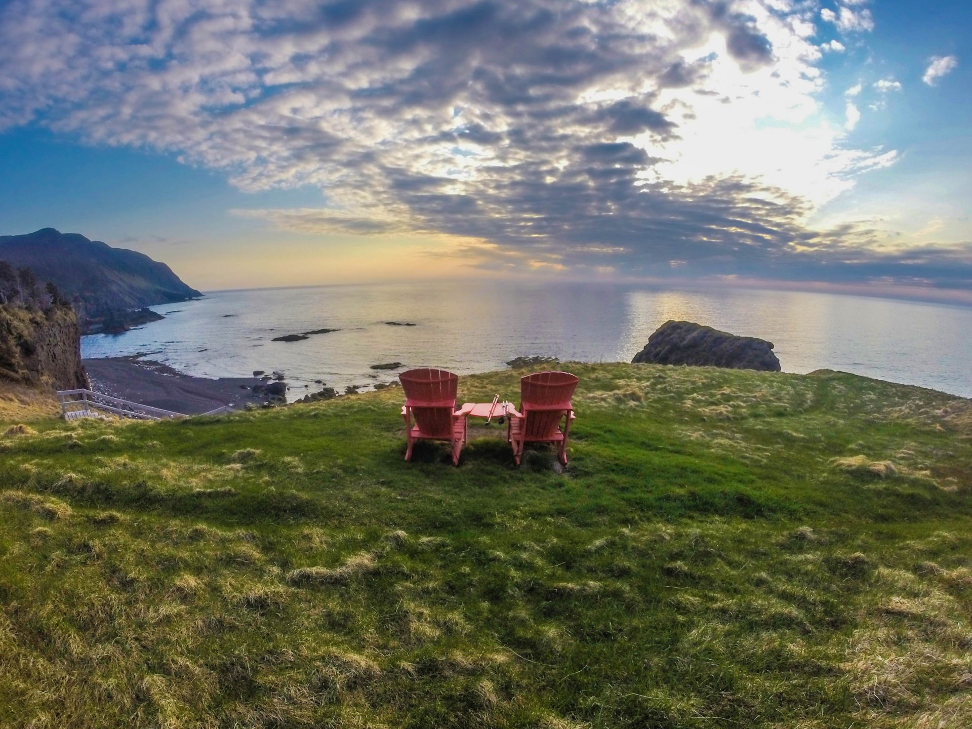 Two muskoka chairs on grass overlooking the ocean from trail at Gros Morne National Park is one of the iconic destinations in Canada.
