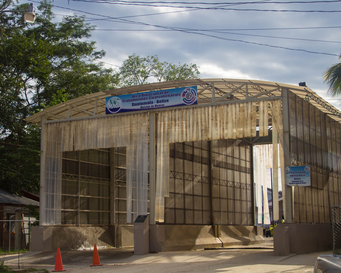 Tall entrances in a wooden shelter mark the border between Belize and Guatemala
