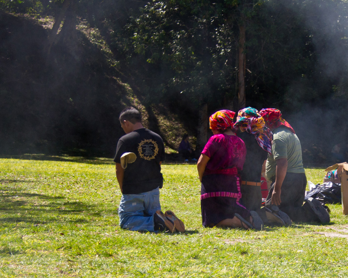 local Mayans prayer while surrounded in smoke near a Mayan ruin