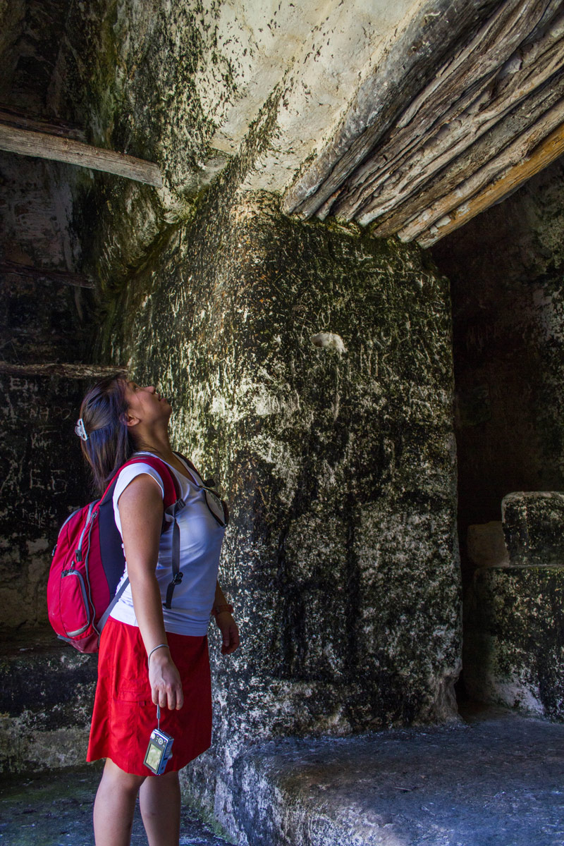 A woman wearing a backpack looks up at a stone door frame in a Mayan ruin