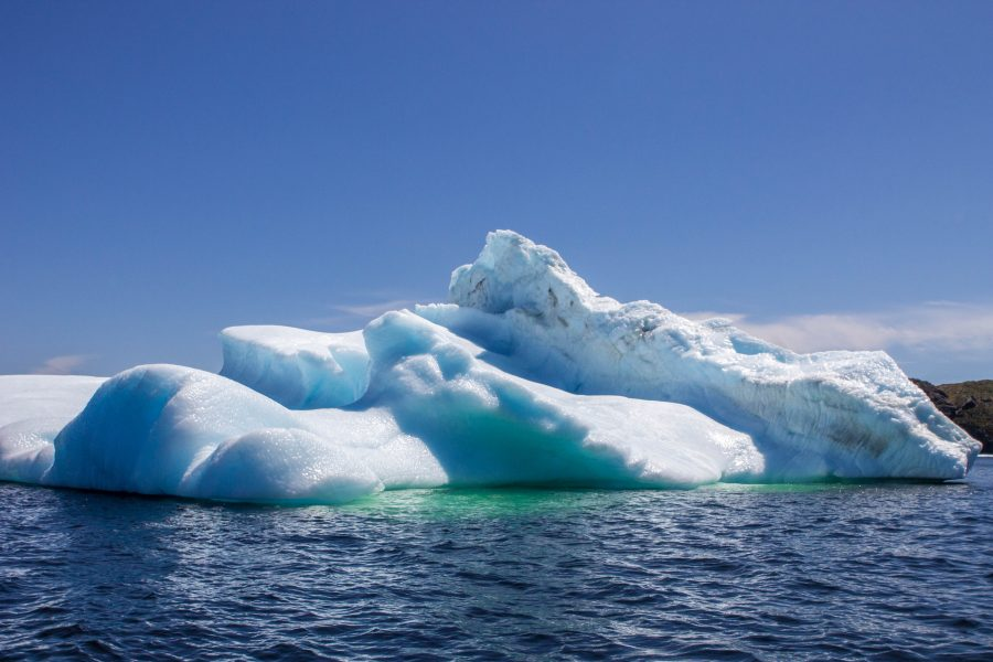 A deeply layered iceberg in the Newfoundland Iceberg Alley with the deepwater showing the depth that the iceberg sinks to - Icebergs in Twillingate