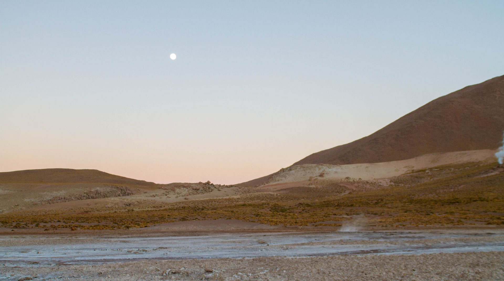El Tatio geyser before sunrise with the moon still in view.