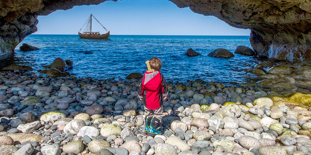 A boy explores the Newfoundland viking trail in Arches Provincial Park