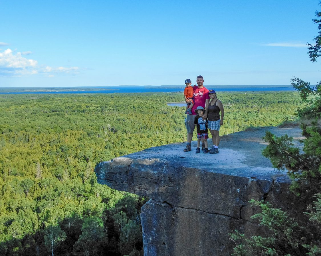 Family picture on the famous lookout at the Cup and Saucer Trail which is one of the Great Spirit Circle Trail Experiences on Manitoulin Island.
