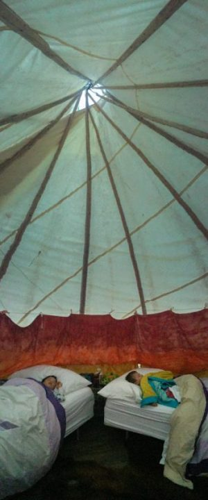 Two young boys sleeping in a bed in a teepee at the Great Spirit Circle Trail glamping site on Manitoulin Island.
