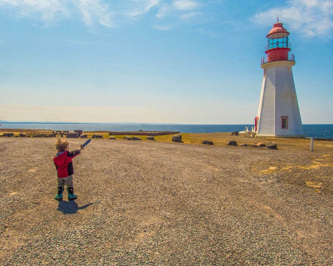 A young boy points a sword at a lighthouse on the coast of Newfoundland - Newfoundland Viking Trail