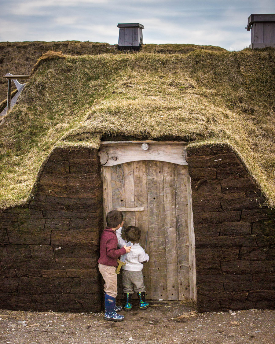Two young boys knock on the door of a Viking house in l'Anse aux Meadows - Newfoundland Viking Trail