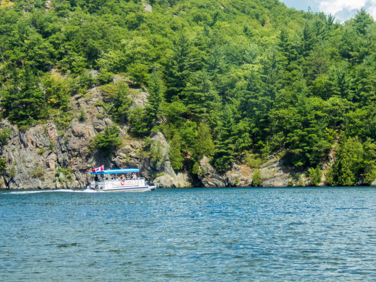 A tour boat drives along the steep cliffs of Bon Echo provincial park - Mazinaw Lake & Cliffs Tour Boat