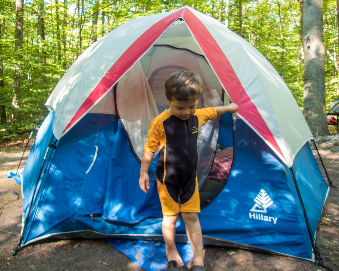 A young boy wearing a wetsuit climbs out of a tent - Top things to do in Bon Echo Provincial Park