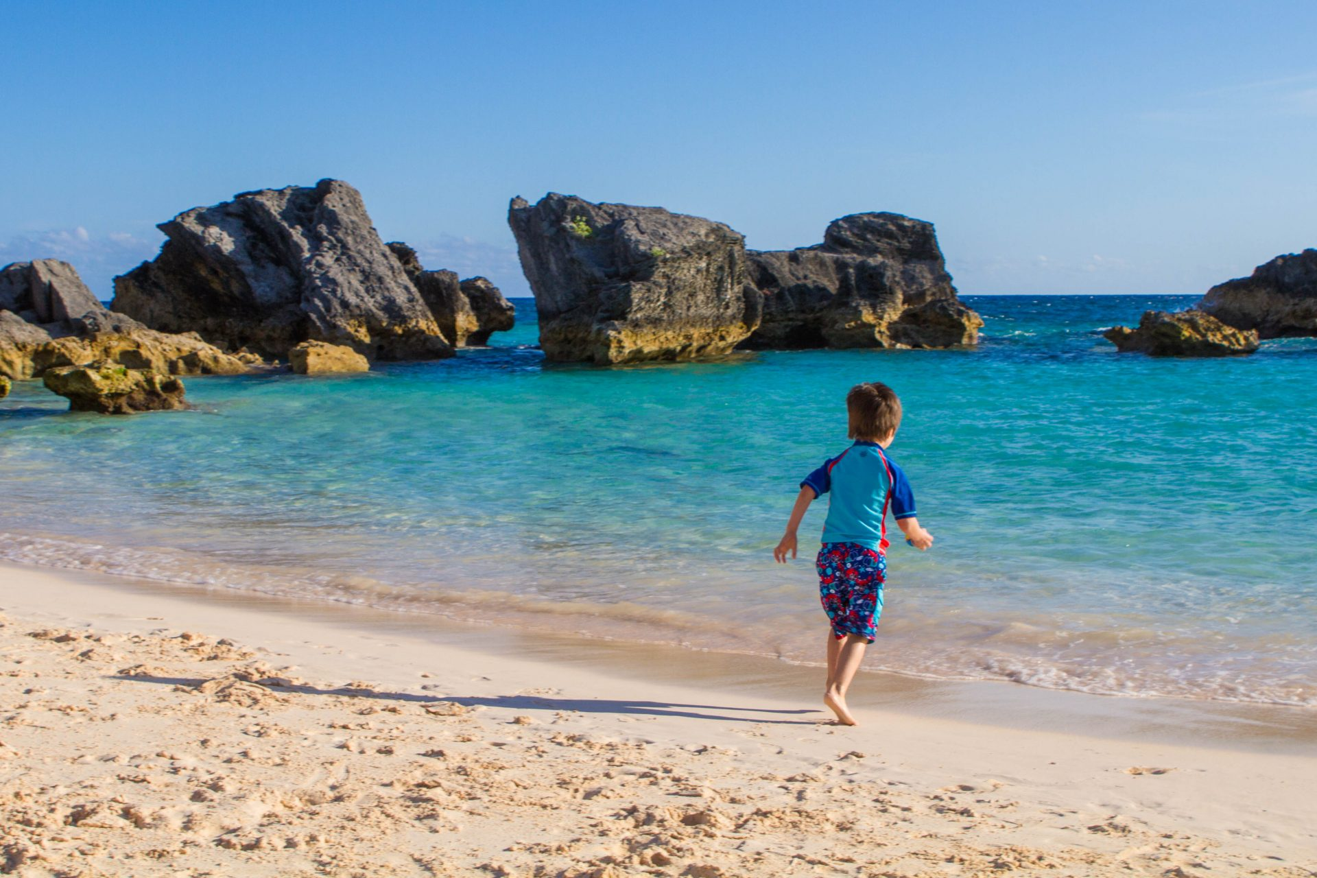 Boy running towards East Whale Beach on our search for the best Bermuda beach.