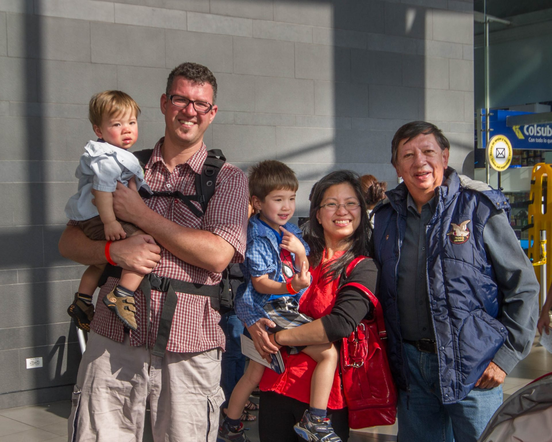 Men, woman and children pose in the Bogota airport.