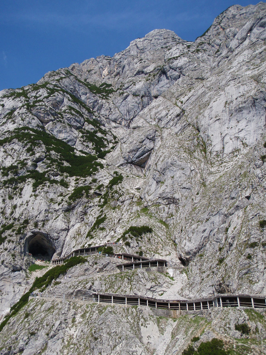A narrow trail winds up a mountain towards a cave entrance - caves you can visit with kids