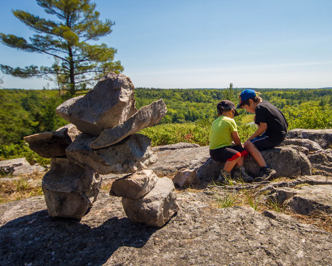 Two young boys play on a rock near a cairn that overlooks forests and lakes - Hiking the Crack in Killarney with Kids