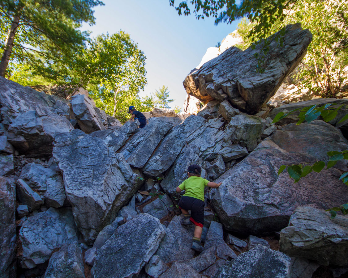 A toddler climbs a large rockfall in Killarney Provincial Park - Hiking the Crack in Killarney with Kids