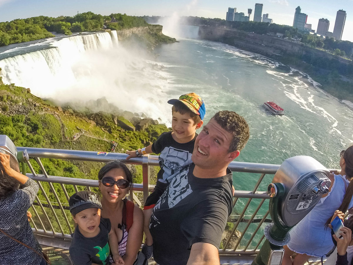A young family smiles up at a camera in front of the American Falls - Exploring Niagara Falls