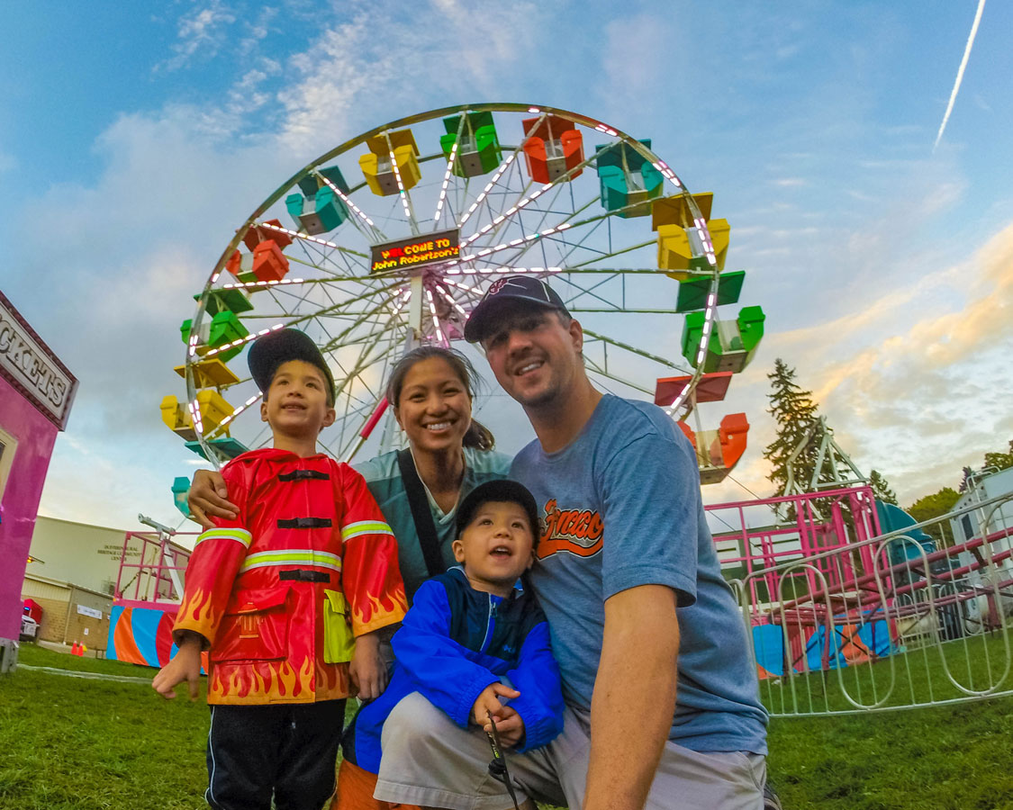 A young family smiling at the camera in front of a colourful Ferris wheel while attending a fall fair, one of the 5 kid-friendly fall activities in Ontario.