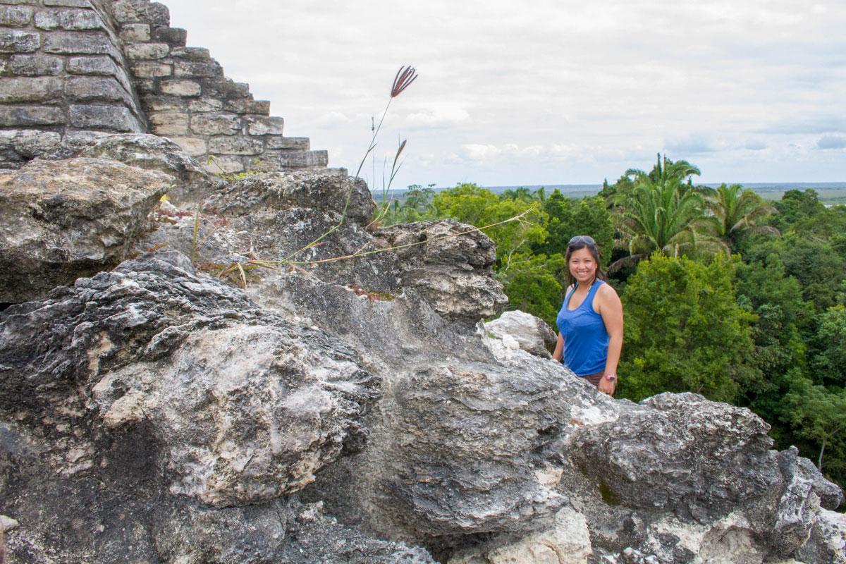 Woman climbing ruins in Lamanai.