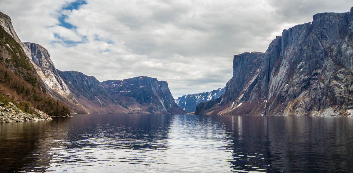 A lake enclosed by the towering granite cliffs of Western Brook Pond in Gros Morne National Park