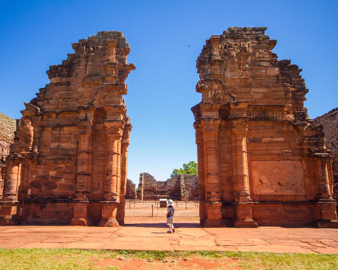 a young boy walks through the tall, intricate walls of San Ignacio Mission in San Ignacio, Argentina