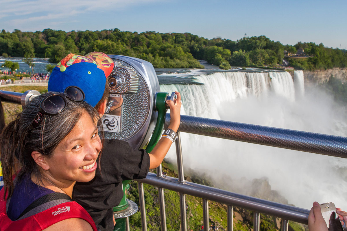 A woman smiles at the camera while her son looks through viewpoint binoculars at Niagara Falls New York