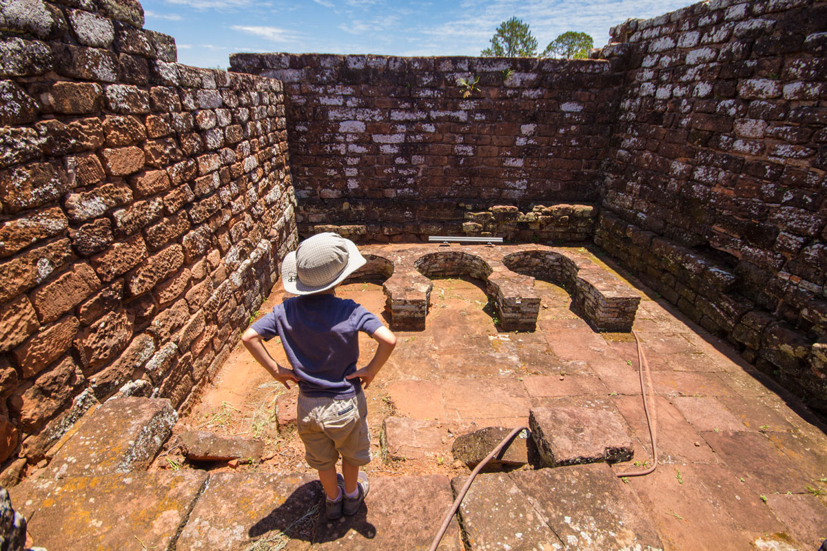 A young boy examines the molds of bells in the workshops of the ruins of Trinidad in Paraguay
