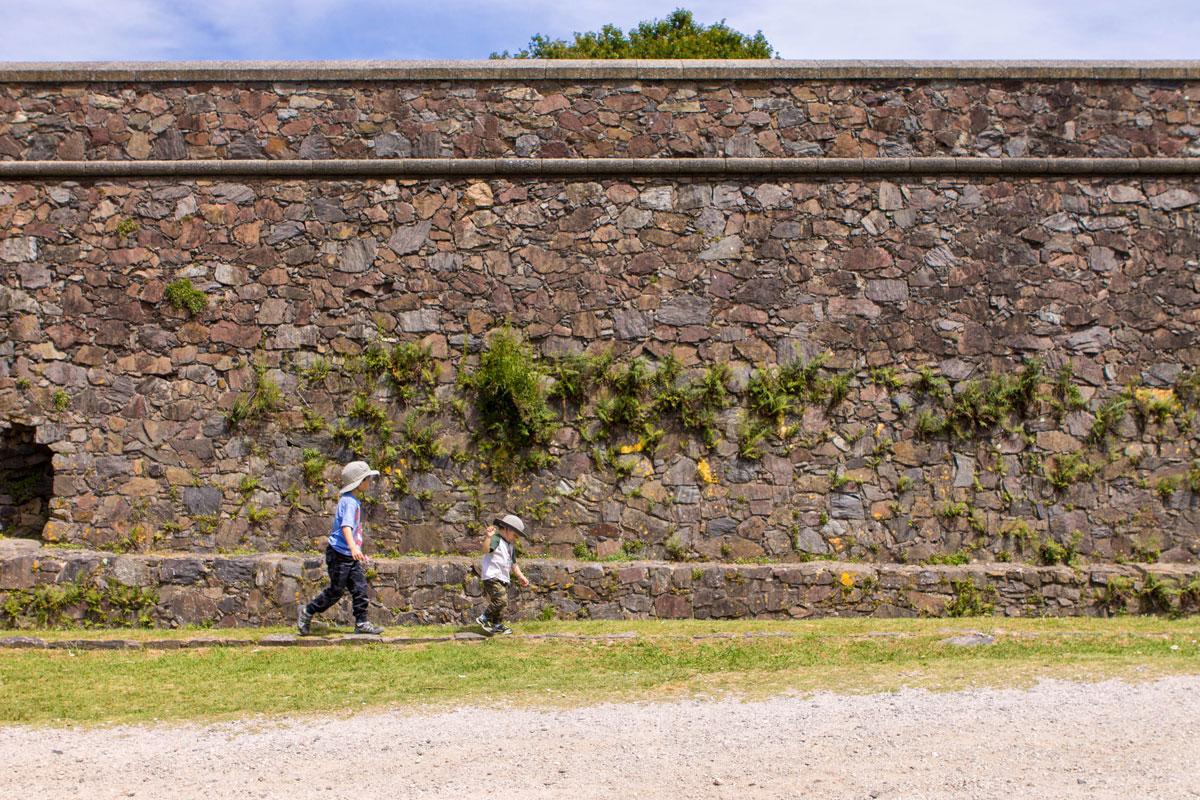 Two boys walking along the outside walls of Barrio Historico of Colonia del Sacramento.