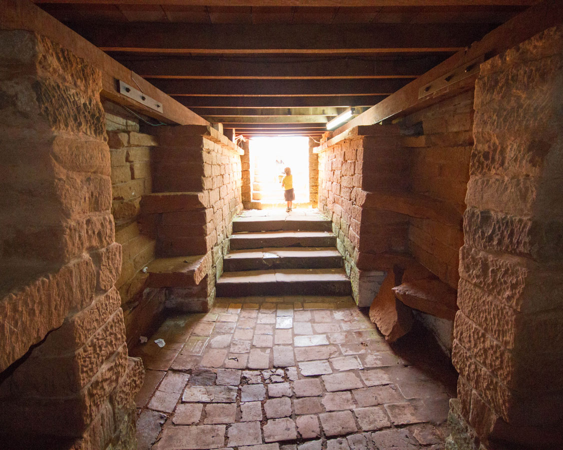 A young boy stands at the entrance of a crypt in the Jesuit ruins in Paraguay