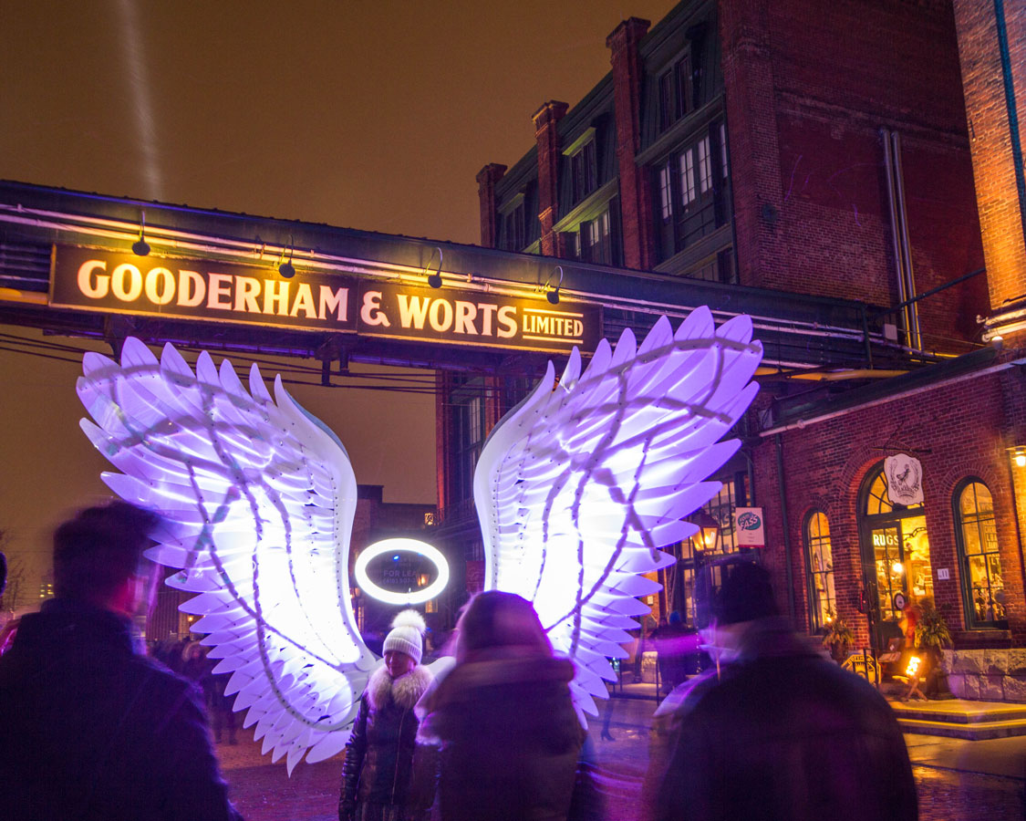 Angel wings and the Gooderham and Worts sign in the Distillery District during the Toronto LightFest
