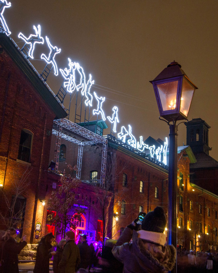 Flame lanterns in the foreground and light art of a parkour artist in the background of the Distillery District during the Toronto LightFest
