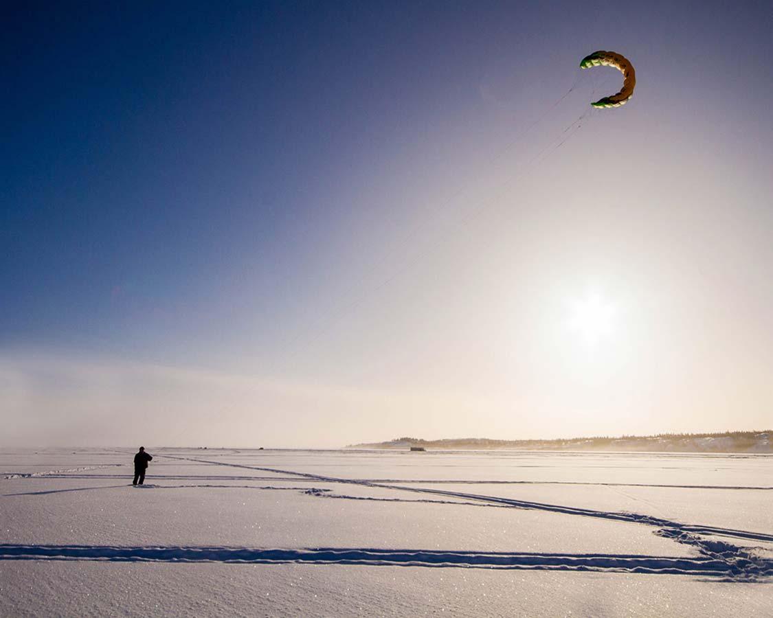 Man kite flying in winter on Great Slave Lake, Yellowknife.