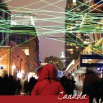 A woman in a red Canada Goose Jacket looks down an alley under a web of green light at the Toronto LightFest in the Distillery District - Pinterest
