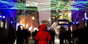 A woman in a red Canada Goose Jacket looks down an alley under a web of green light at the Toronto LightFest in the Distillery District