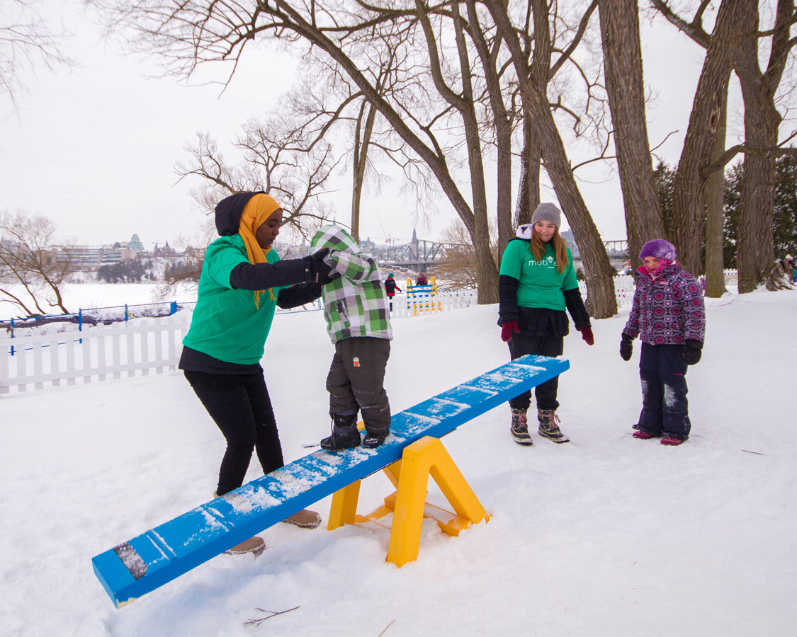 Boy crossing a seesaw as part of an obstacle course at Winterlude.