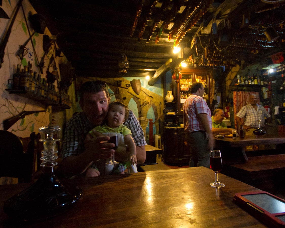 A man holds his baby in the bar Ibn Errik Rex, famous for Ginja in Obidos, Portugal